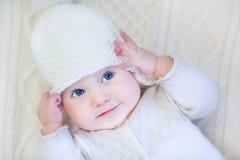 戴被编织的毛线衣和帽子的女婴 库存图片
