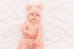 被编织的熊帽子和裤子的逗人喜爱的矮小的女婴 图库摄影