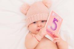 戴被编织的熊帽子的逗人喜爱的女婴拿着卡片 免版税库存图片
