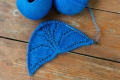被编织的羊毛半圆蓝色布料和针在木桌上 免版税库存照片