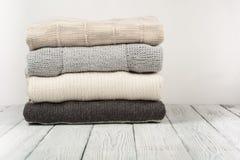 被编织的羊毛毛线衣 堆被编织的冬天在木背景,毛线衣,针织品,文本的空间穿衣 免版税库存图片