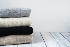 被编织的羊毛毛线衣 堆被编织的冬天在木背景,毛线衣,针织品,文本的空间穿衣 免版税图库摄影