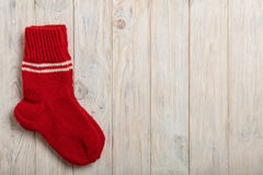 被编织的羊毛殴打在轻的木背景的红颜色 免版税库存照片