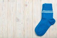 被编织的羊毛殴打在轻的木背景的蓝色 库存图片