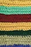 被编织的美好的羊毛服装五颜六色的条纹背景自然纹理,黄色,灰棕色,深紫红色,蓝色,绿色围巾宏指令特写镜头 免版税库存照片