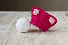 被编织的钩针编织小桃红色猫帽子 妇女` s男女平等主义者行军抗议创造性的工艺工作的猫帽子 免版税图库摄影