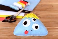 被缝的毛毡玩具,螺纹成套工具,剪刀,毛毡在木背景覆盖 软的滑稽的蓝色妖怪 免版税库存照片