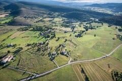 被耕的土地、路和私有房子俯视图  免版税库存照片