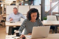 被聚焦的女实业家在一台膝上型计算机的工作在办公室 免版税图库摄影