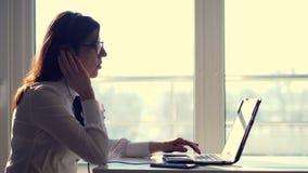 被聚焦的殷勤女性成功的调度员,佩带的耳机,看看侧视图屏幕,研究计算机 股票录像