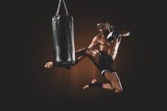被聚焦的泰拳战斗机实践的反撞力侧视图在沙袋的 免版税库存照片