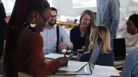 被聚焦的黑人年轻女人与膝上型计算机一起使用,愉快的不同种族的微笑的商人在现代办公室合作 股票录像