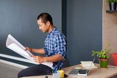 被聚焦的年轻亚洲建筑师读书在办公室计划 免版税库存照片