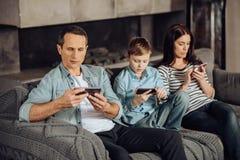 被胶合对他们的电话的年轻家庭 库存图片