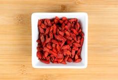 被脱水的红色goji莓果宏指令在白色碗的 库存图片