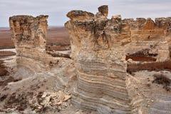 被腐蚀的石灰石柱子和堆在荒地 库存图片