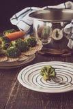 被蒸的菜用在一把叉子的硬花甘蓝在木桌上 免版税库存图片