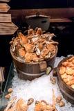 被蒸的螃蟹和大虾在冰在木桶有方向的 免版税库存图片