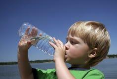 被装瓶的男孩饮用水 库存照片