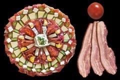 被装饰的开胃菜美味盘用在黑背景和西红柿隔绝的三个猪肚烟肉更卤莽 图库摄影