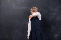 被触犯的女小学生站立在黑板 库存图片