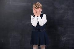 被触犯的女小学生站立在黑板 免版税库存照片