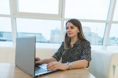 被设想的妇女自由职业者为在一个咖啡馆的一台膝上型计算机工作与一时髦的intrerer 图库摄影