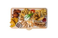 被设置的啤酒快餐 鸡快餐在切板服务,隔绝在白色背景 免版税库存图片