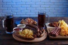 被设置的开胃啤酒快餐 猪肉切片、烤香肠和fr 免版税库存照片
