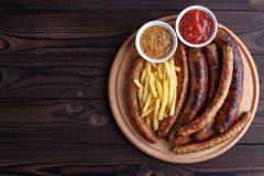 被设置的开胃啤酒快餐 被盘问的香肠和炸薯条se 库存照片