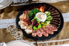 被设置的开胃肉:发牢骚切片、烟肉、蒜味咸腊肠和菜o 图库摄影