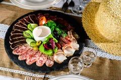 被设置的开胃肉:发牢骚切片、烟肉、蒜味咸腊肠和菜o 免版税库存照片