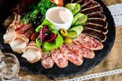 被设置的开胃肉:发牢骚切片、烟肉、蒜味咸腊肠和菜o 库存照片