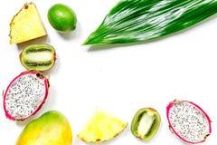 被设置的异乎寻常的果子 Dragonfruit、菠萝、芒果、石灰和猕猴桃在白色背景顶视图copyspace 免版税库存照片