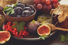 被设置的收获:李子、葡萄、无花果、荚莲属的植物莓果、核桃、蜂蜜和果酱玻璃 免版税库存图片