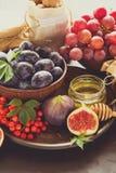 被设置的收获:李子、葡萄、无花果、荚莲属的植物莓果、核桃、蜂蜜和果酱玻璃 免版税图库摄影