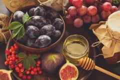 被设置的收获:李子、葡萄、无花果、荚莲属的植物莓果、核桃、蜂蜜和果酱玻璃 免版税库存照片