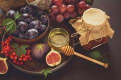被设置的收获:李子、葡萄、无花果、荚莲属的植物莓果、核桃、蜂蜜和果酱玻璃 库存图片