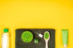 被设置的温泉:肥皂、面具、油、海盐和毛巾在黄色背景 免版税库存照片