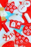 被设置的美丽的圣诞节装饰 毛毡房子、圣诞树、星、球、棒棒糖,雪人装饰,红色和白色螺纹 免版税图库摄影