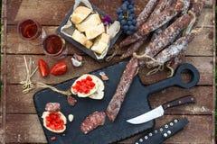 被设置的酒和开胃菜 面包,烘干被治疗的猪肉香肠、蕃茄在土气木服务板和红葡萄酒在玻璃 免版税图库摄影