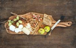 被设置的酒开胃菜:乳酪选择,蜂蜜,葡萄,杏仁,核桃,面包条,在橄榄色的木服务的无花果上 免版税库存照片