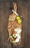 被设置的酒开胃菜:乳酪选择,蜂蜜,葡萄,杏仁,核桃,面包条,在橄榄色的木服务的无花果上 免版税图库摄影