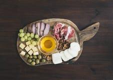 被设置的酒开胃菜:肉和乳酪选择,蜂蜜,葡萄, w 免版税库存照片