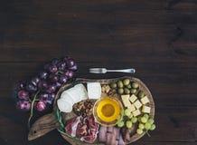 被设置的酒开胃菜:肉和乳酪选择,蜂蜜,葡萄 免版税库存图片