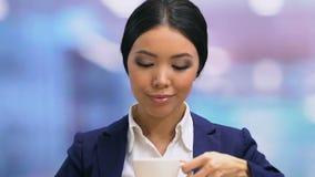 被超载的女性雇员结束膝上型计算机,饮用的茶和考虑家 股票录像