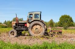 被转动的农业拖拉机使用在土豆领域 免版税库存照片