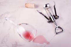 被转动的酒杯和拔塞螺旋在大理石背景/转动了红酒酒杯和拔塞螺旋在大理石背景 r 免版税库存图片
