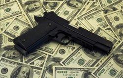 被过滤的黑枪手枪和金钱美元背景 图库摄影
