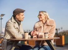 被迷恋的夫妇坐在桌和饮用的浓咖啡上户外 免版税库存照片